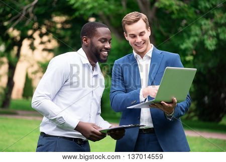 Do it with pleasure. Pleasant cheerful content colleagues using laptop and discussing project while standing outside