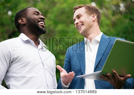 Have some fun. Cheerful smiling delighted colleagues laughing and using laptop while standing outside