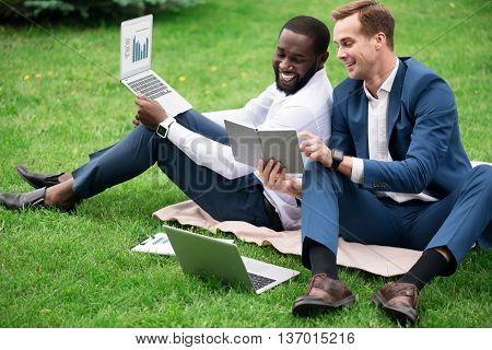 In a good mood. Cheerful smiling overjoyed colleagues sitting on the grass and using laptops while discussing project