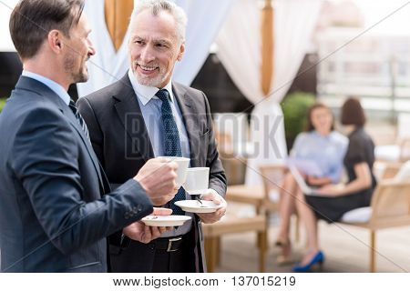 Get some rest. Positive delighted smiling colleague having a nice conversation and drinking coffee while beautiful women sitting on the couch in the background