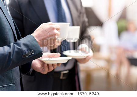 Enjoy the aroma. Close up of cup of coffee in hands of pleasant man holding and drinking it while talking with his colleague