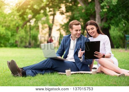 Refresh your mind. Positive delighted smiling colleagues sitting on the grass and working on the project while using laptop