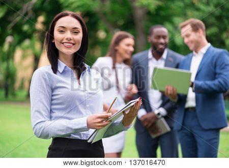 Ready to work. Cheerful charming woman smiling and holding papers while her colleagues using laptop in the background