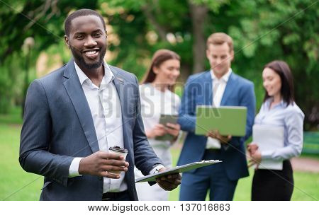 Express yourself. Positive delighted smiling man drinking coffee and holding folder while his colleagues