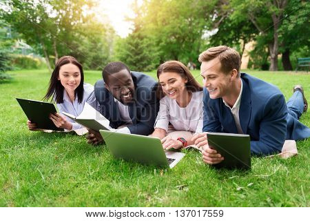 Refresh your mind. Positive delighted colleagues resting on the grass and smiling while using laptop