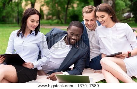 Pleasant relaxation. Positive content smiling colleagues lying on the grass and using laptop while resting together