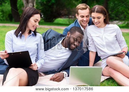 Closer to nature. Positive smiling colleagues sitting on the blanket and using laptop while resting outdoor