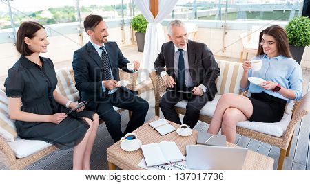 Elated atmosphere. Cheerful content smiling colleagues sitting at the table and drinking coffee while resting after work