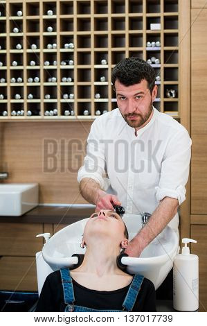 Handsome hairdresser is washing female hair with concentration. He is holding a water tap. The woman is leaning her head on sink and looking at the man