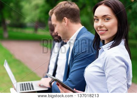 Full of joy. Cheerful delighted beautiful woman holding tablet and sitting on the bench while her colleagues talking in the background