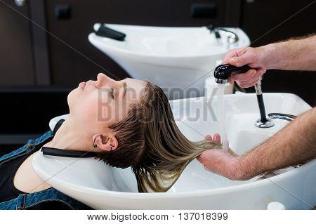Hair care in modern spa salon. Male hairdresser washing teen girl's hairs.