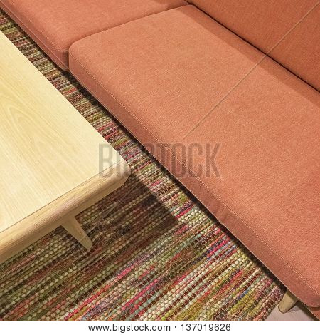 Salmon color sofa and wooden coffee table. Living room detail.