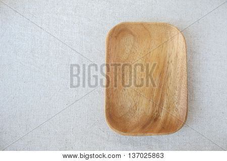 Empty wooden plate on linen table background for food display montage