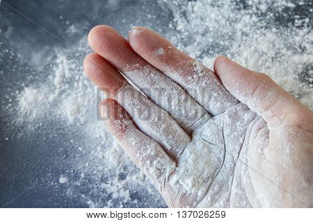 Talcum powder on one hand over black background