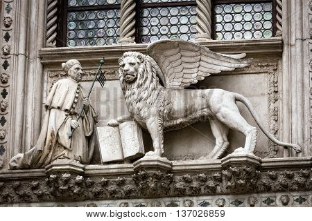 Statue of the Doge Francesco Foscari (1423-1457) kneeling before the Lion of St. Mark on the Doge Palace facade in Venice Italy