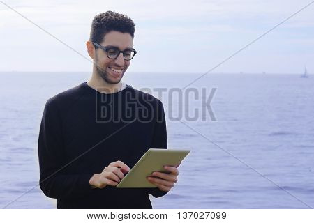 Young Man Using A Tablet Outdoors