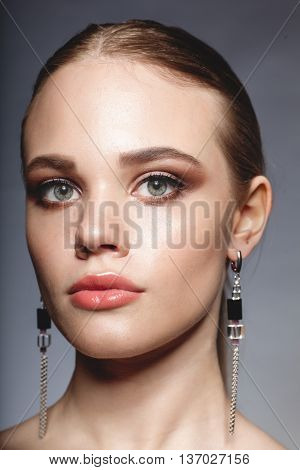 close-up beauty portrait of young caucasian blonde female model on studio gray background