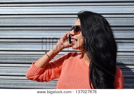 Young beautiful latin woman talking on the phone. Woman using a cellphone wearing casual clothes.