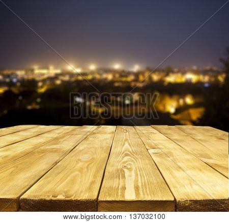 The wooden table and view on city at night who shines