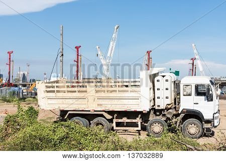 Heavy modern truck is parking near the construction site in the city.