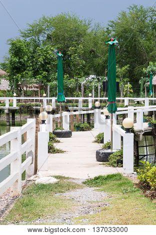 White concrete bridge over the small pond in the local farm