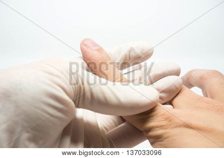 doctor with examination glove holding patient injury finger