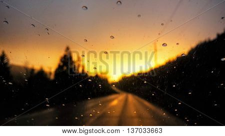 Glowing Orange Sunset Focused on Windscreen Raindrops