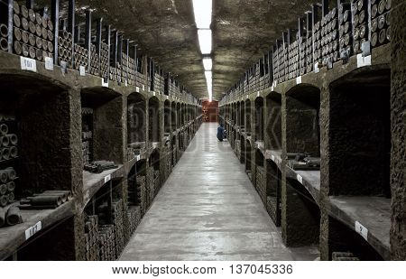 Crimea Russia - June 10 2015: Large wine-cellar with racks of dusty bottles of aged wine. Stone long shelves.