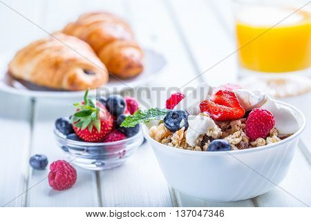 Muesli with yogurt and berries on a wooden table. Healthy fruit milk yogurth and cereal brakfast.