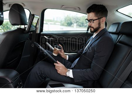 Business executive reading information on tablet when sitting in car