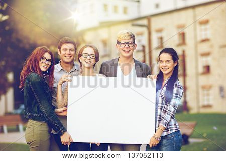 education, campus, friendship and people concept - group of happy teenage students holding big white blank billboard