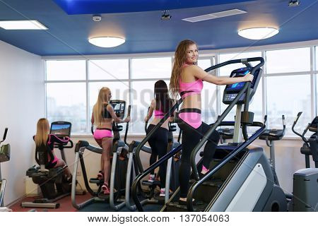 Image of workout in gym. Pretty girl posing at camera
