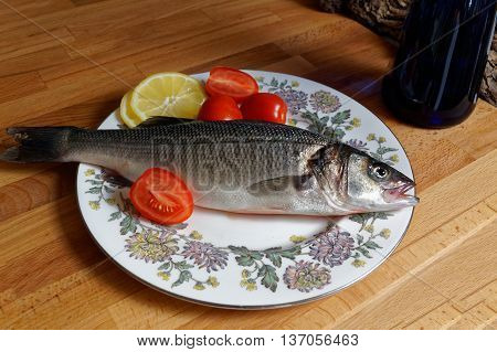 Sea bass spigola. Fresh fish with the head on plate. Kitchen table home cooking.