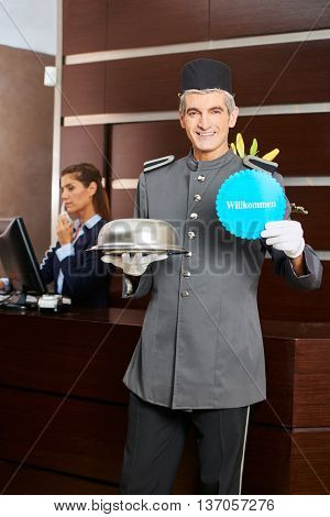 Hotel page holding German sign saying