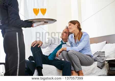Hotel page serving drinks to business couple in a hotel room