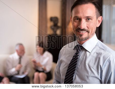 Epitome of manhood. Pleasant delighted handsome man smiling and expressing gladness while his colleagues sitting on the couch in the background poster
