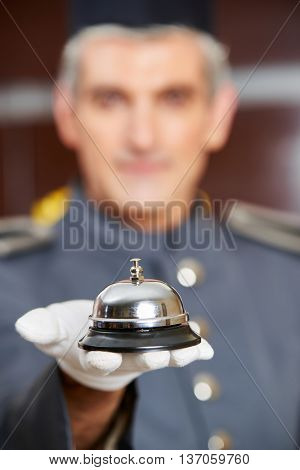 Concierge holding hotel bell on his hand with gloves