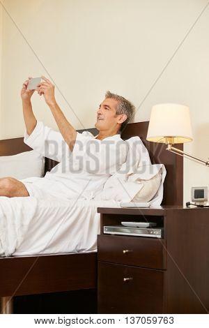 Smiling elderly man in hotel room taking selfie with his smartphone