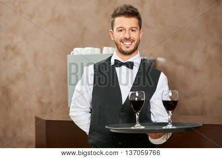 Smiling waiter in uniform serving red wine in a hotel restaurant