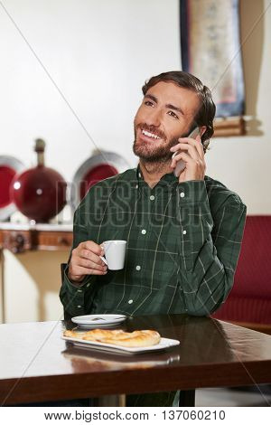 Man in hotel drinking espresso and making a phone call with his smartphone