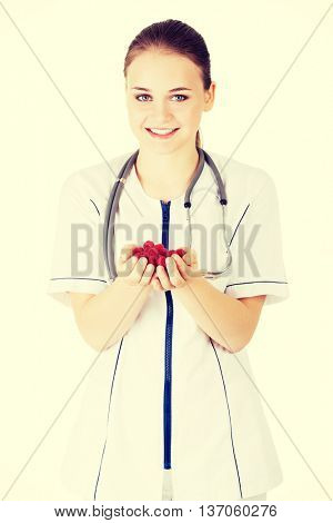 Female doctor holding raspberries in hand.