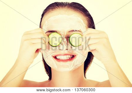 Young woman with cucumber slices