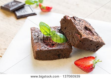 Close up of chocolate brownie cakes topped with strawberries and arranged on baking paper