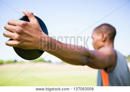 Close-up of athlete holding a discus in stadium