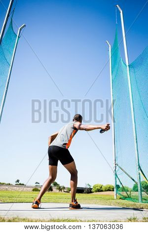 Rear view of athlete about to throw a discus in stadium