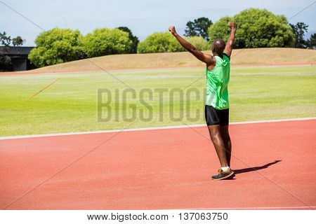 Rear view of athlete posing after victory on racing track