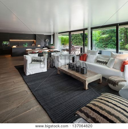 Modern living room with white divans and big windows