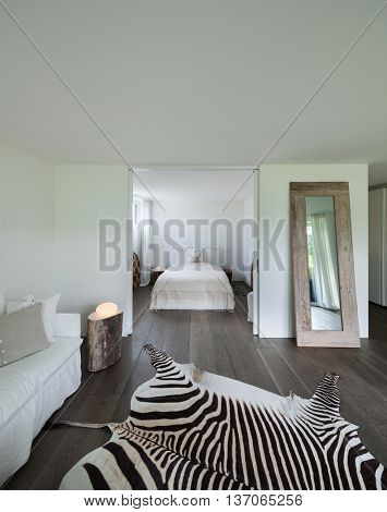 living room with bedroom view, leather zebra on the floor, white walls