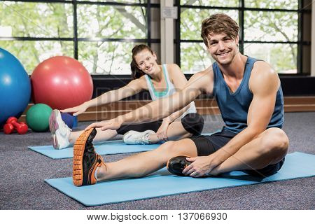Portrait of man and woman performing fitness exercise at gym