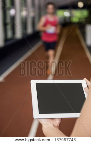 Trainer using a digital tablet while man performing running exercise in gym